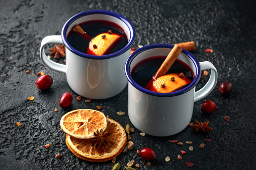 Mulled wine in white rustic mugs with spices and orange fruit