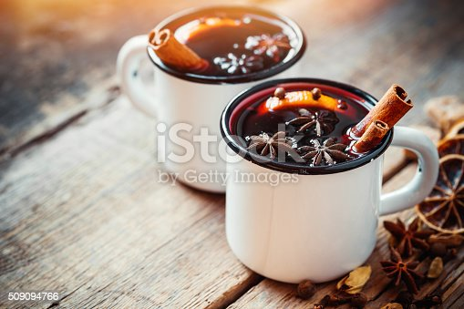 Mulled wine in white rustic mugs with spices and citrus