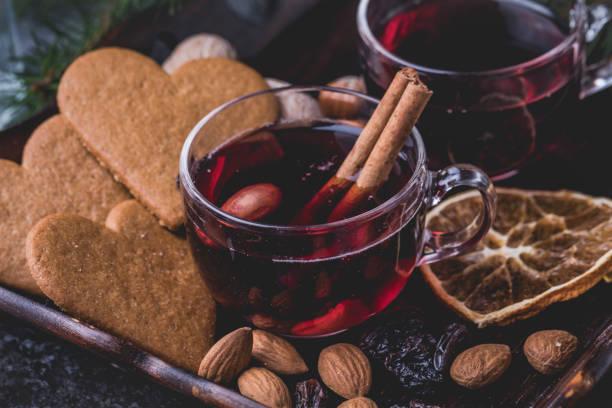 kalp ile mulled şarap şeklinde gingerbread çerezleri, badem, kuru üzüm ve dilimlenmiş portakal kurutulmuş. - glühwein stok fotoğraflar ve resimler