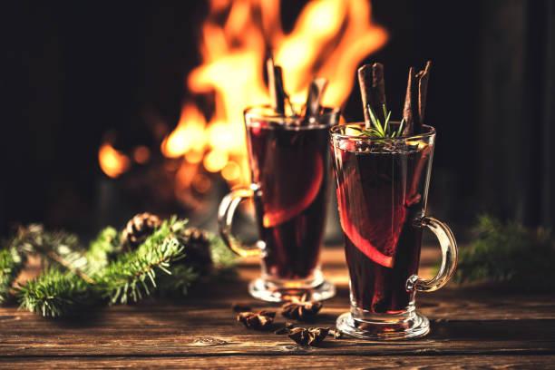 glühwein met specerijen in glazen op een houten tafel tegen de achtergrond van een open haardvuur. winter drink traditioneel voor de kerst vakantie. - gluhwein stockfoto's en -beelden