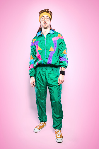 A cool, funky young adult in late 1980's / early 1990's fashion style, with mullet, fluorescent colored track suit, nerdy glasses, and sweat band.  Vibrant pink background. Vertical portrait.