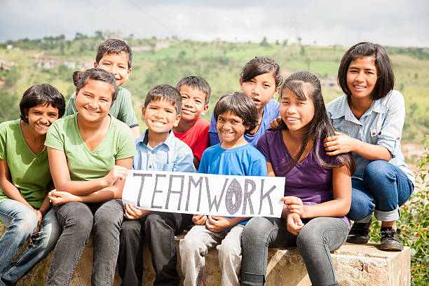 Mult-ethnic, large group of children hold 'teamwork' sign outdoors. Multi-ethnic and mixed aged group of children holding a white, sign outdoors that reads
