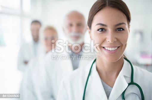 Closeup portrait of group of mixed age team of doctors in a line at a local hospital. There are two senior colleagues, a man in mid 30's and the person in focus is charming female nurse in mid 20's. Looking at camera and smiling.