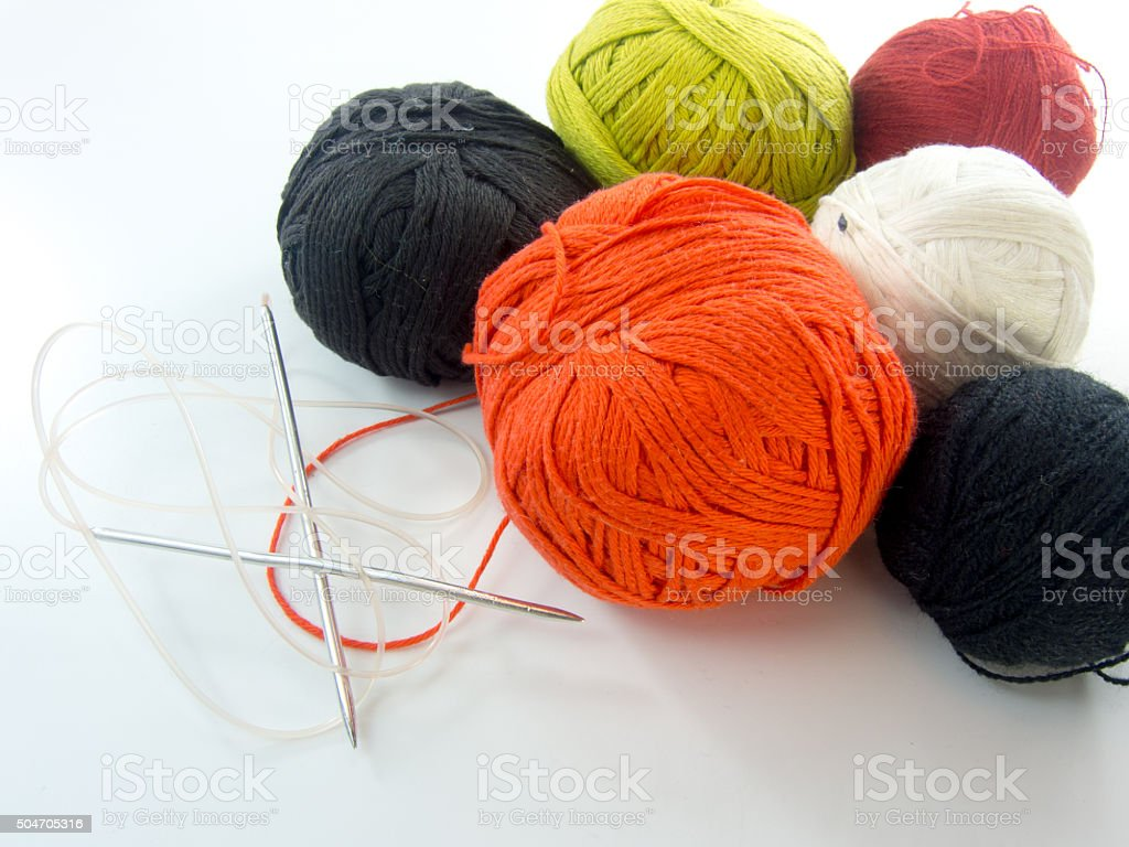 multi color balls of wool and knitting needles over white stock photo