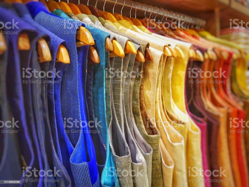 multi color dress sherwani kurta hanging from hangar in a garment shop for sale stock photo