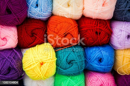 Close up image depicting multi colored balls of wool for sale at the art and craft store. The balls of wool are displayed stacked on top of each other and in a row. Room for copy space.