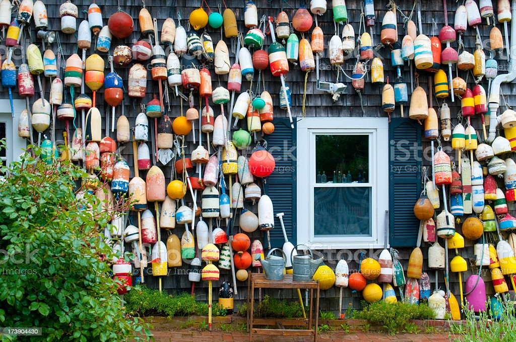 Multi colored buoys hanging on a house stock photo