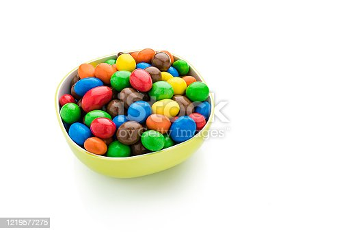 High angle view of multi colored chocolate candies in a bowl isolated on white background. High resolution 42Mp studio digital capture taken with SONY A7rII and Zeiss Batis 40mm F2.0 CF lens
