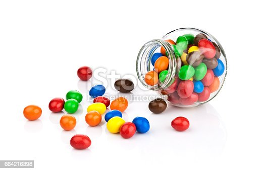 Open candy jar filled with multi colored chocolate covered peanut candies on white background. Some candies are spilled out of the jar directly on the background. DSRL studio photo taken with Canon EOS 5D Mk II and Canon EF 70-200mm f/2.8L IS II USM Telephoto Zoom Lens