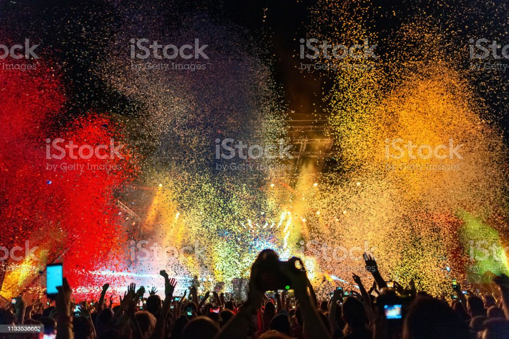 Multi colored confetti above the crowd on music festival. royalty-free stock photo