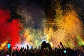 Crowd of people having fun while watching colorful confetti fireworks at music festival.
