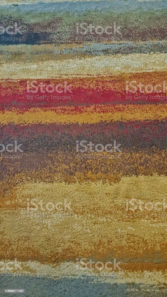 Vertical image of a thin carpet section with layered multi colored...