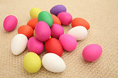 Multi colored easter eggs against a natural beige woven matt background.
