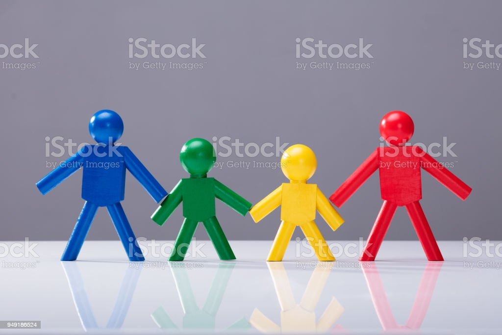 Multi Colored Human Figures Standing In A Row stock photo