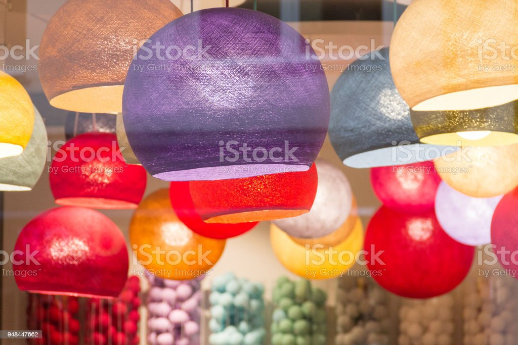 Multi colored lit lampshades in a store stock photo