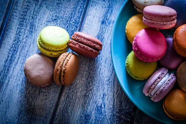 multi colorido biscoitos em um prato azul atirou de cima na tabela azul - macaroon - fotografias e filmes do acervo