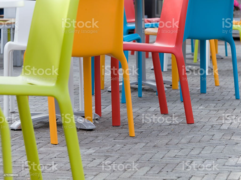 Superbe Multi Colored Outdoor Chairs On Gray Paving Stones Royalty Free Stock Photo