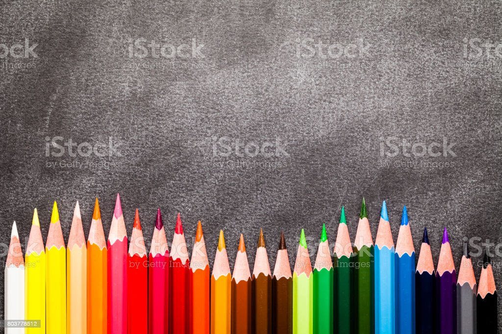 Multi colored pencils making a wave shot from above stock photo