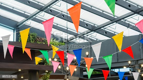 istock Multi colored triangle flags hanging indoor party 532037552
