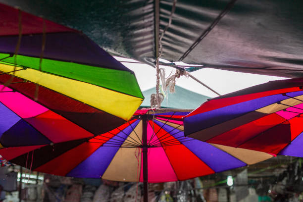 Multi colored umbrellas on the ceiling of a street market in Bangkok, Thailand stock photo
