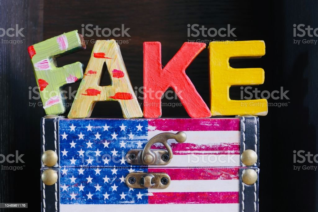 Multi colored word Fake on american flag stock photo