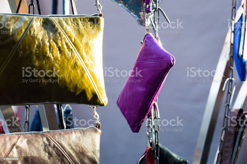 Multi coloured handmade leather womens handbags in a row at the market, London, UK stock photo