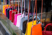 Multi coloured handmade leather womens handbags in a row at the market, London, UK