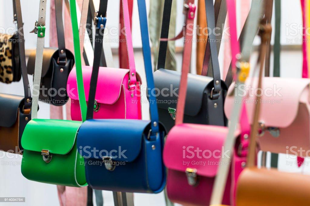 Multi coloured handmade leather womens handbags in a row stock photo