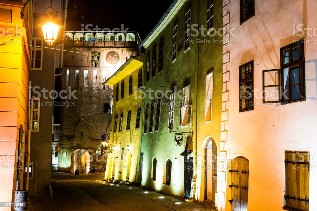 Multi coloured houses and clock tower illuminated at night in Sighisoara old town, Transylvania, Romania stock photo