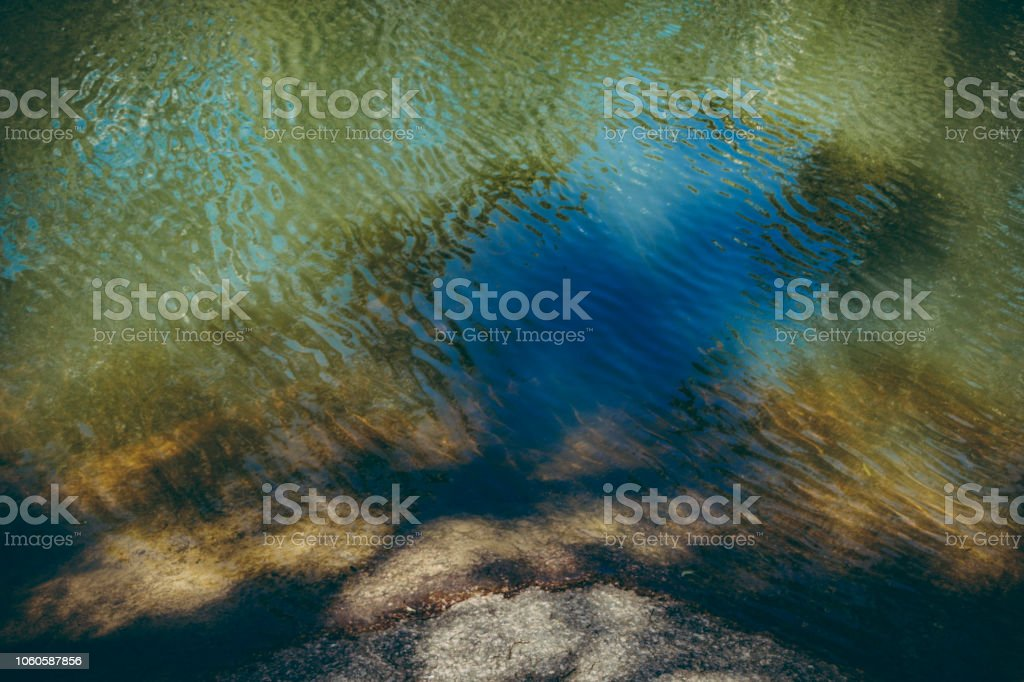 Multi coloured reflection in a creek bed stock photo