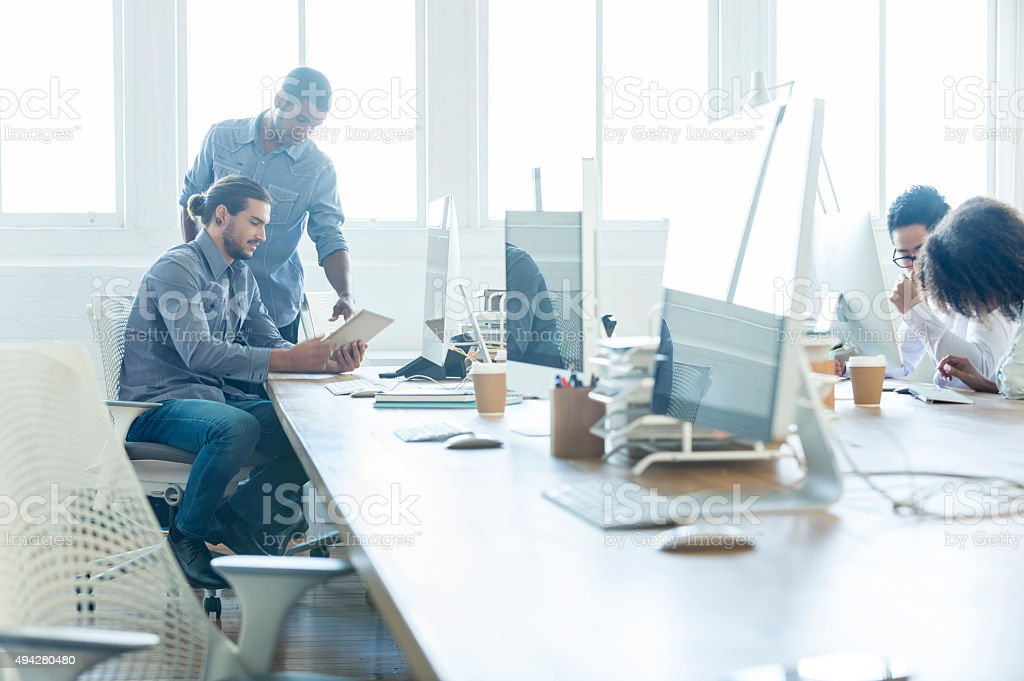 Multi cultural group working with technology in a studio. stock photo
