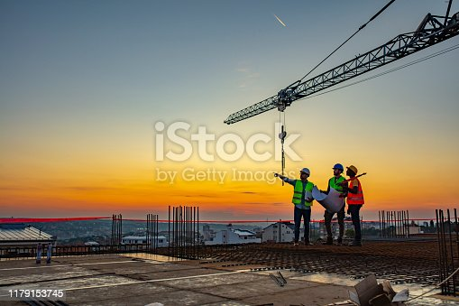 Three Multi-Ethnic construction workers in uniform standing at construction site with crane in background, discussing building plans while holding blueprint at sunset under the tower crane.