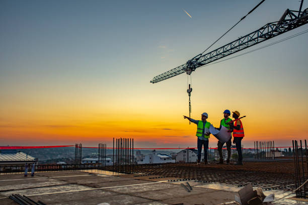 Multi ethic workers talking at construction site reviewing plans Three Multi-Ethnic construction workers in uniform standing at construction site with crane in background, discussing building plans while holding blueprint at sunset under the tower crane. engineer stock pictures, royalty-free photos & images