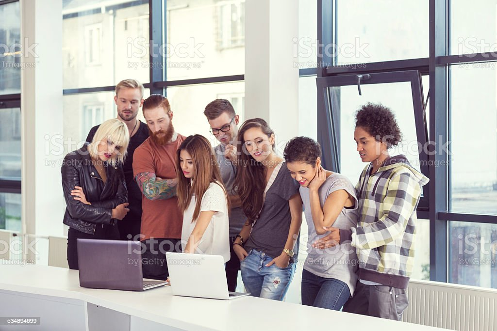 Multi ethnic busienss team meeting Multi ethnic business team brainstorming in an office, watching projects on laptops.  2015 Stock Photo