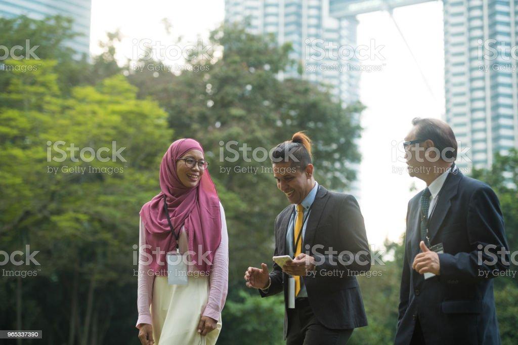 Multi ethnic business team having a walking meeting royalty-free stock photo