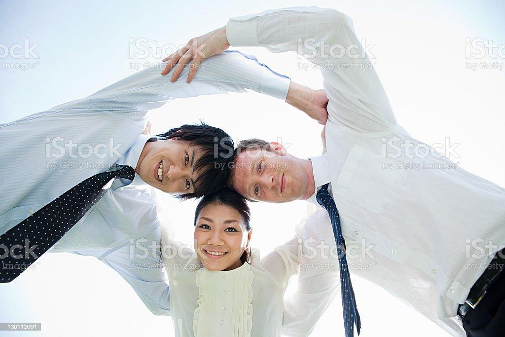 Multi ethnic businesspeople in huddle stock photo