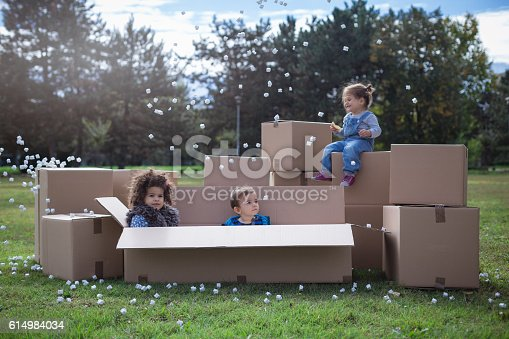 istock multi ethnic children playing with cardboard boxes 614984034