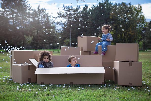 multi ethnic children playing with cardboard boxes - vorschuldekorationen stock-fotos und bilder