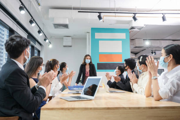 Multi ethnic colleagues celebrating with applauding the female executive while meeting in new normal office. Business team wearing face mask stock photo