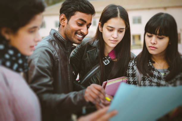 Multi ethnic college students discussing project together. stock photo