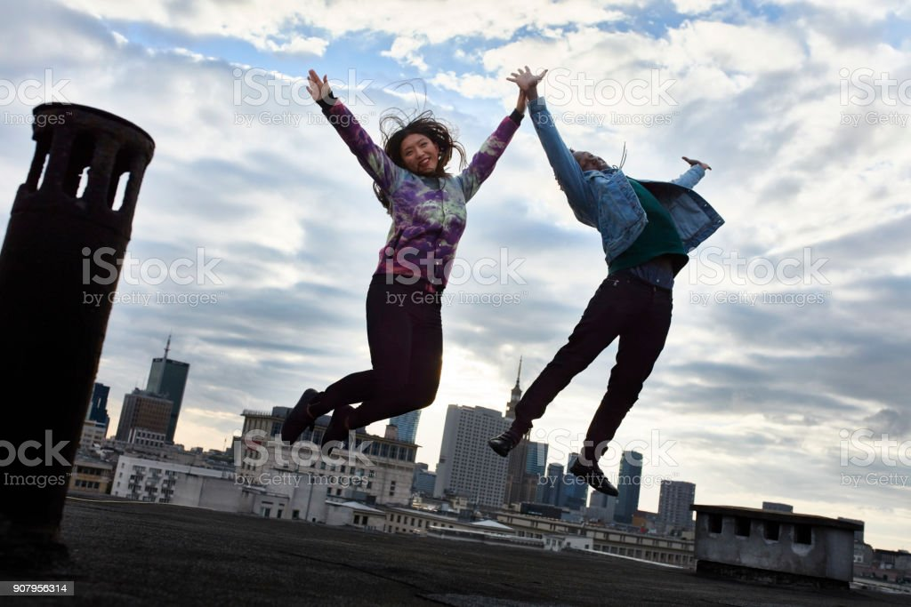 Multi ethnic couple having fun on the rooftop. High five stock photo