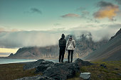 Couple on an Icelandic beach. Mountain range in background
