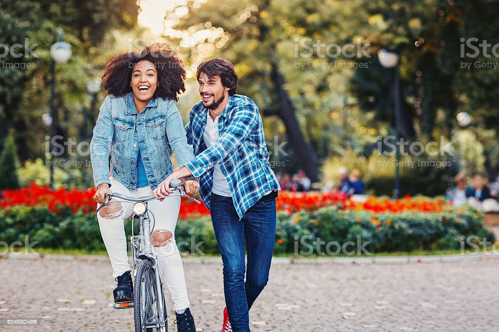 Multi ethnic couple with a bike stock photo