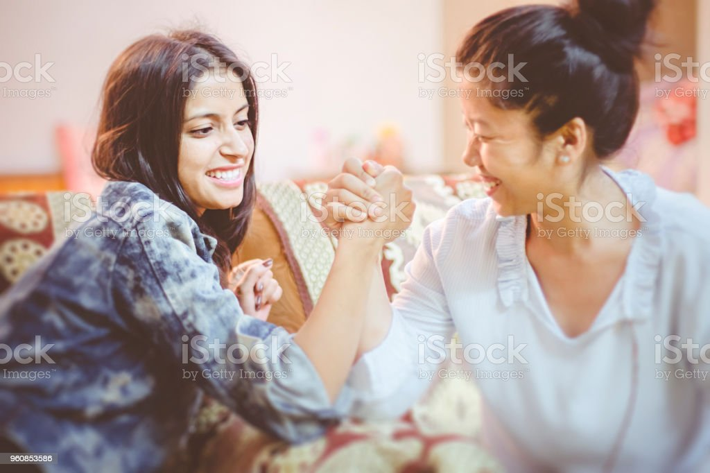 Multi ethnic female friends doing arm wrestling at home. stock photo