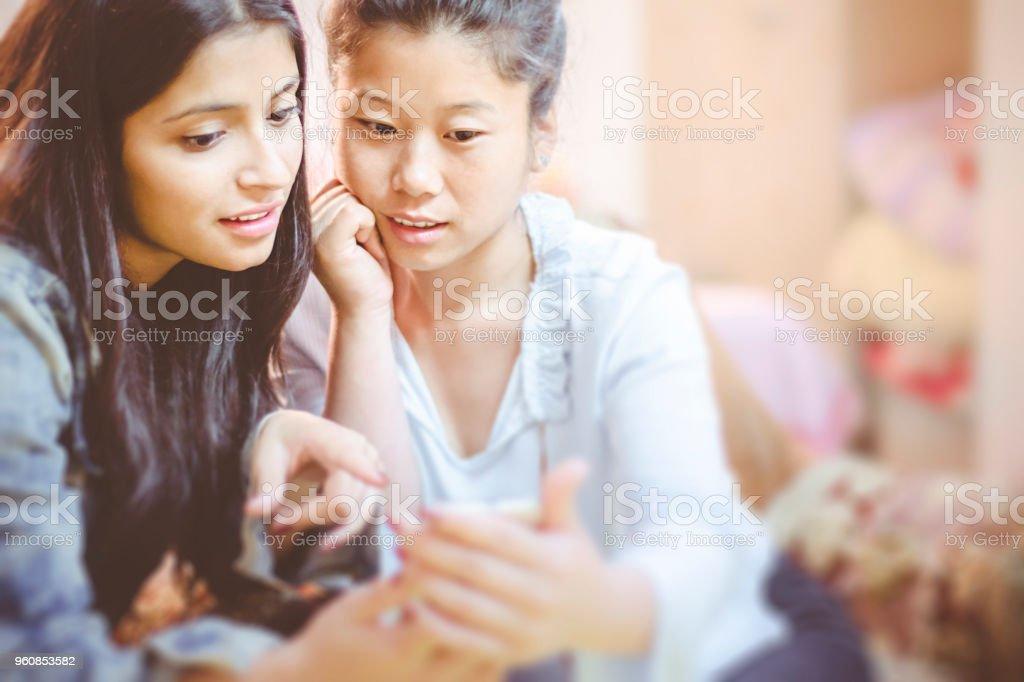 Multi ethnic female friends sharing mobile phone. stock photo