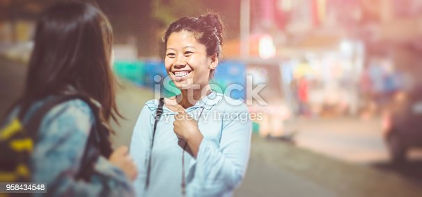Asian, Indian multi ethnic female friend together on city street. They are having fun and enjoying their leisure time while walking and talking on street at night. This panoramic image is also suitable for banner because of more copy space.