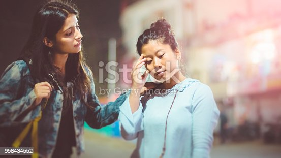Asian, Indian multi ethnic female friend standing together on city street in evening and one friends is consoling other who is  sad.