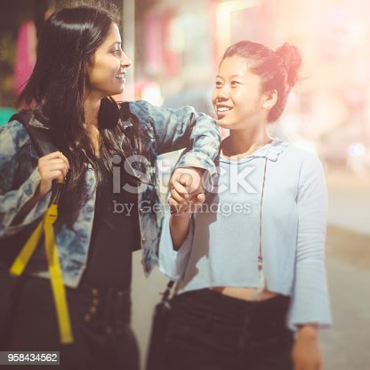Asian, Indian multi ethnic female friend together on city street. They are having fun and enjoying their leisure time while walking and talking on street at night.