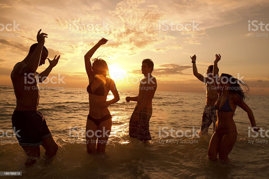 Multi ethnic friends dancing on the beach royalty-free stock photo