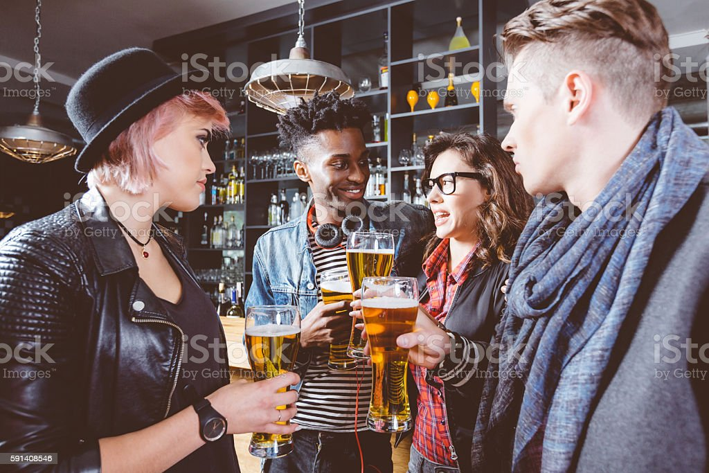 Multi ethnic friends drinking  beer in a pub Multi ethnic group of happy friends - caucasian and afro american - drinking beer in the pub, talking. Adult Stock Photo